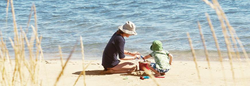 Mor og barn leker på stranden