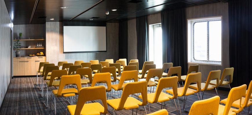 møterom med gule stoler og vindu ut mot havet