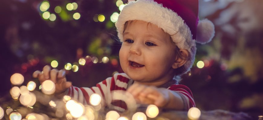 barnehagebarn med nisselue ved juletreet